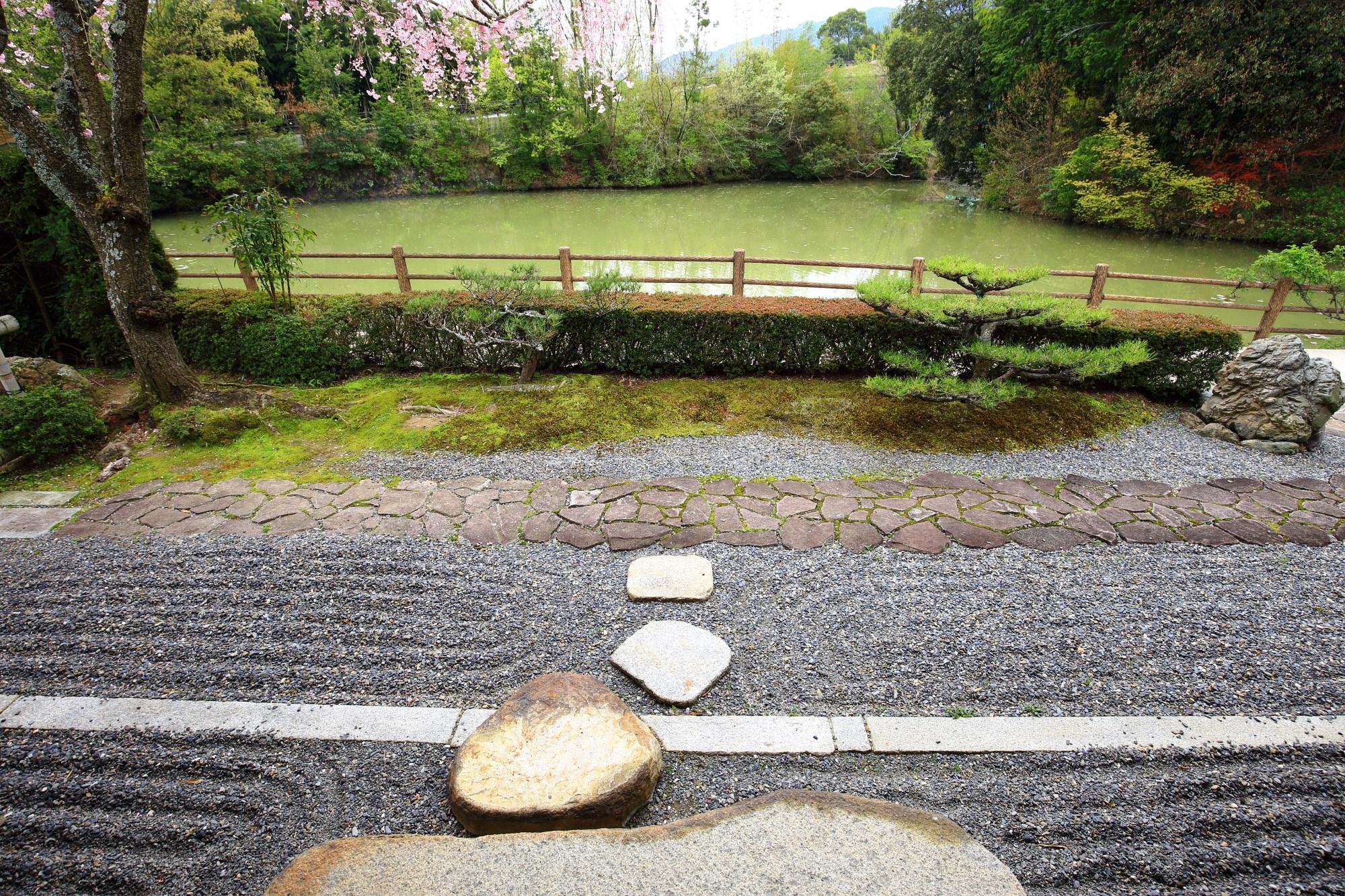 波文様の砂と石畳の参道の向こうには池が広がる正法寺の南側の庭園